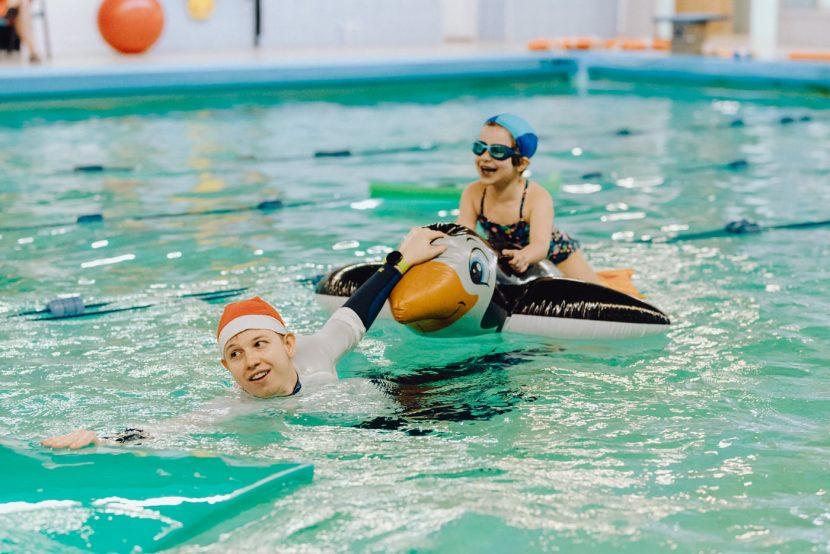 Instruktor prowadzi dmuchanego pingwina z dziewczynką