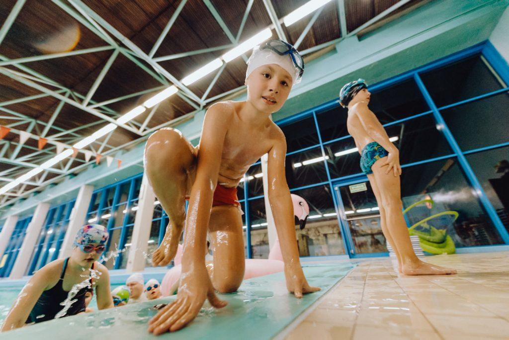 Chłopiec wychodzi mokry z basenu