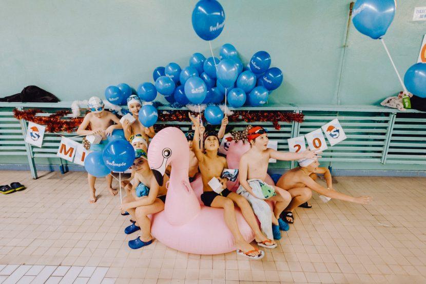 Dzieciaki na dmuchanym flamingu z niebieskimi balonami