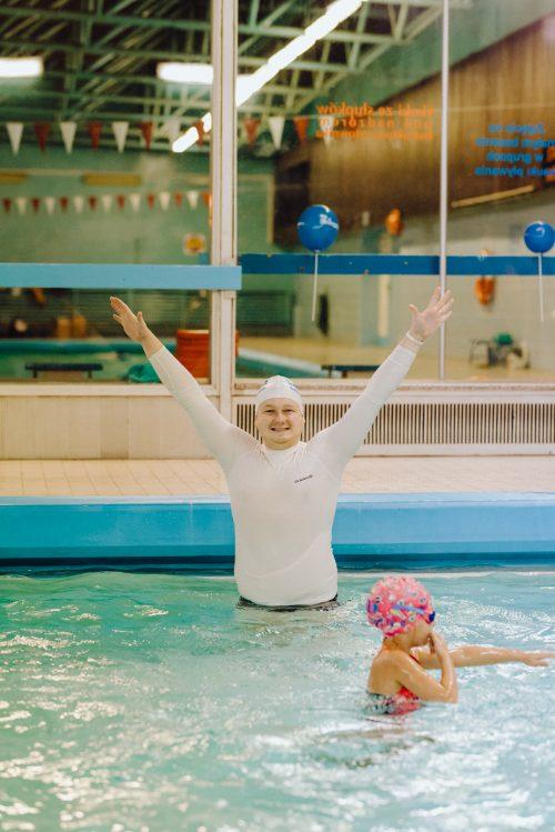 Instruktor pływania w białym stroju trzyma ręce w górze
