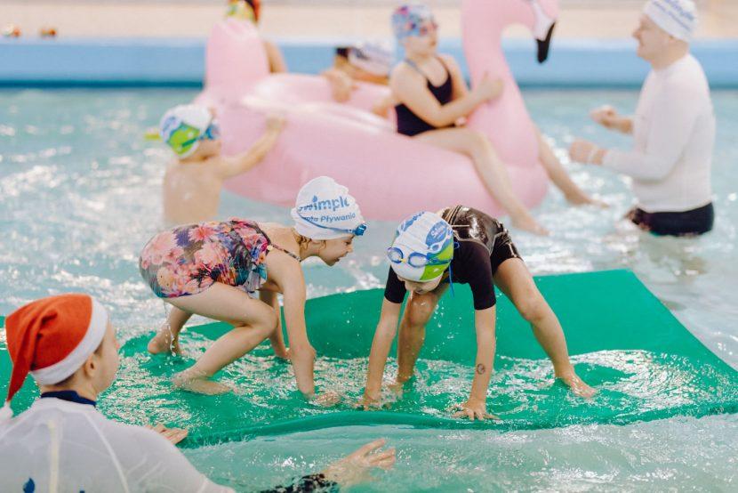 Dzieci próbują ustać na zielonej tratwie z pianki na basenie