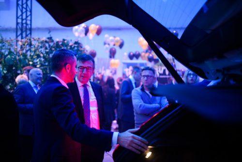 mężczyżni oglądają bagażnik auta
