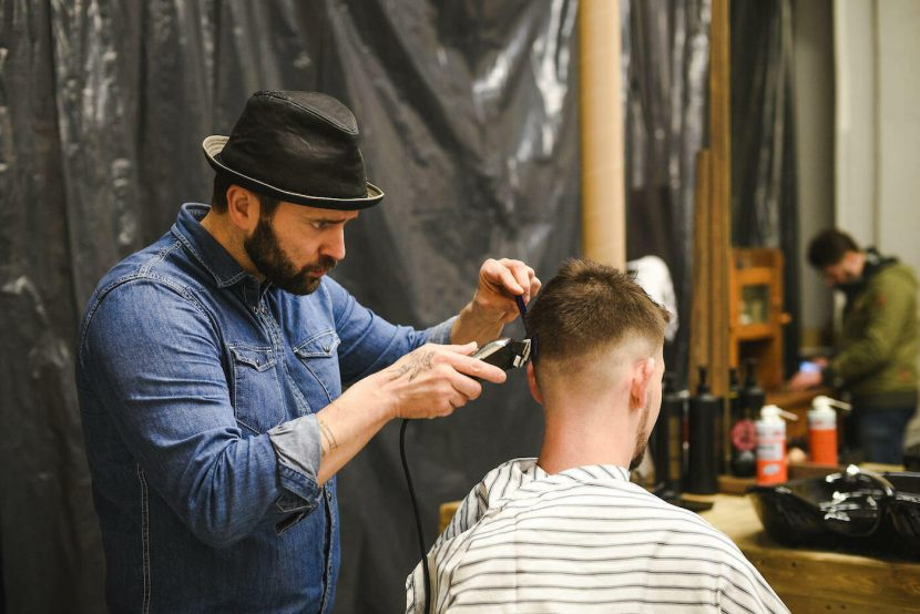 Barber w czarnym obcina klienta shaverem