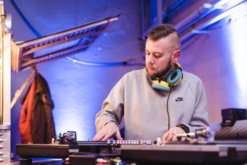 DJ w szarej bluzie gra muzykę