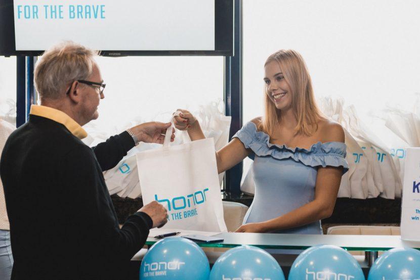 Hostess w niebieskiej sukience daje mężczyźnie prezent powitalny