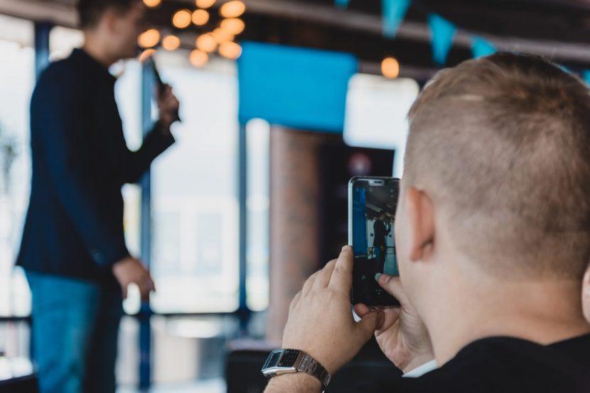 Mężczyzna robi zdjęcie prowadzącemu telefonem
