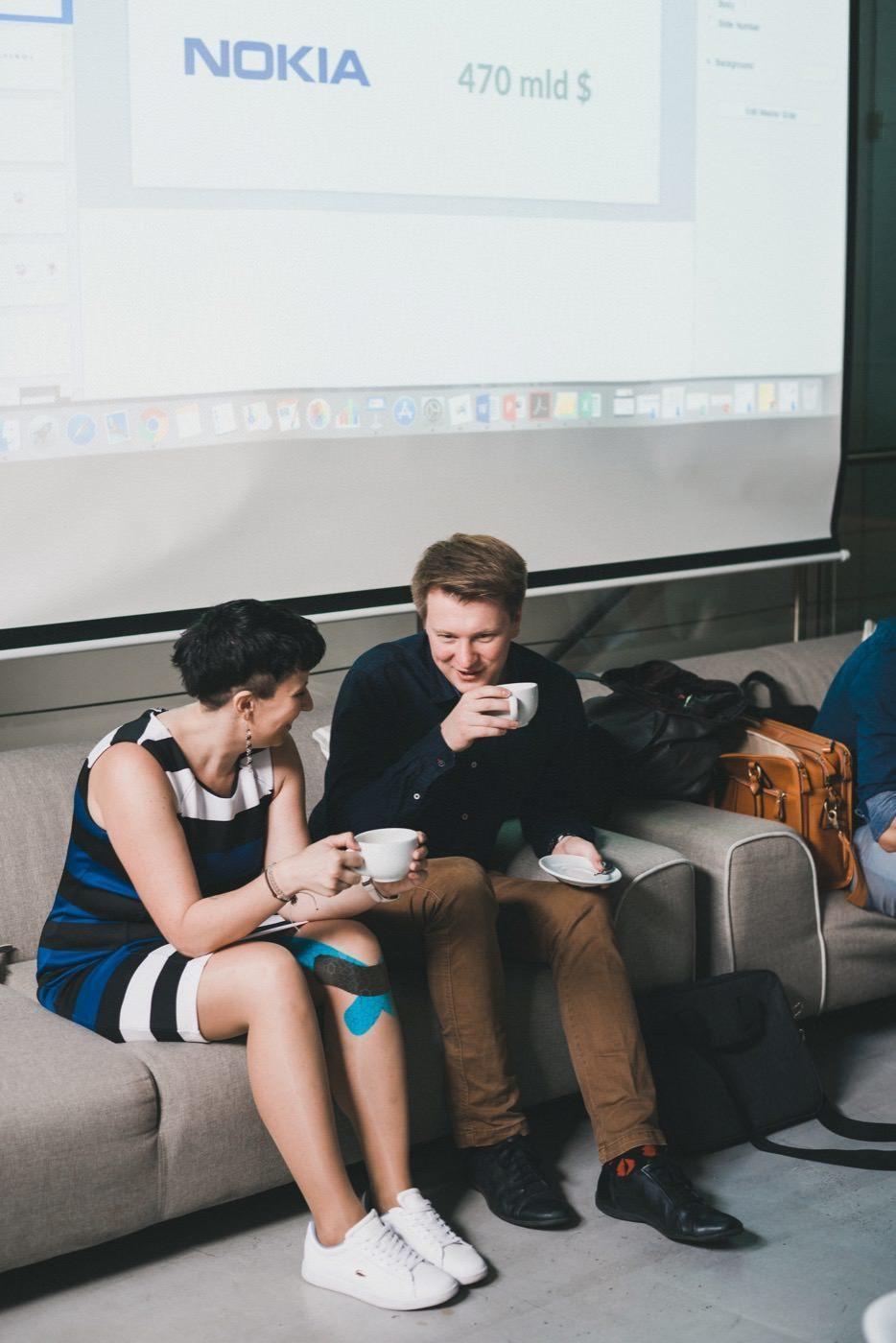 Dziewczyna i chłopak rozmawiają na szarej kanapie