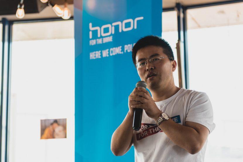Mężczyzna z mikrofonem w ręku na tle logo marki honor