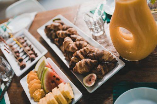 Mini rogaliki owoce i sok pomarańczowy na drewnianym stole