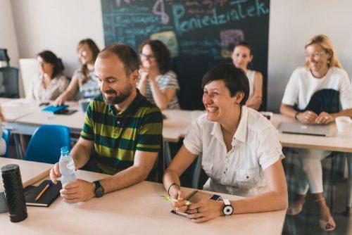 Mężczyzna w koszulce w zielone paski trzyma wodę a kobieta w białej koszulce śmieje się trzymając długopis