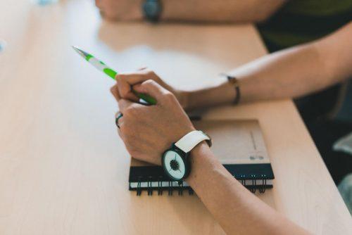 Dłonie kobiety trzymające zielony długopis, na ręku biały designerski zegarek