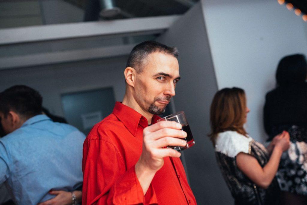 Mężczyzna w czerwonej koszuli ze szklanką whisky z colą
