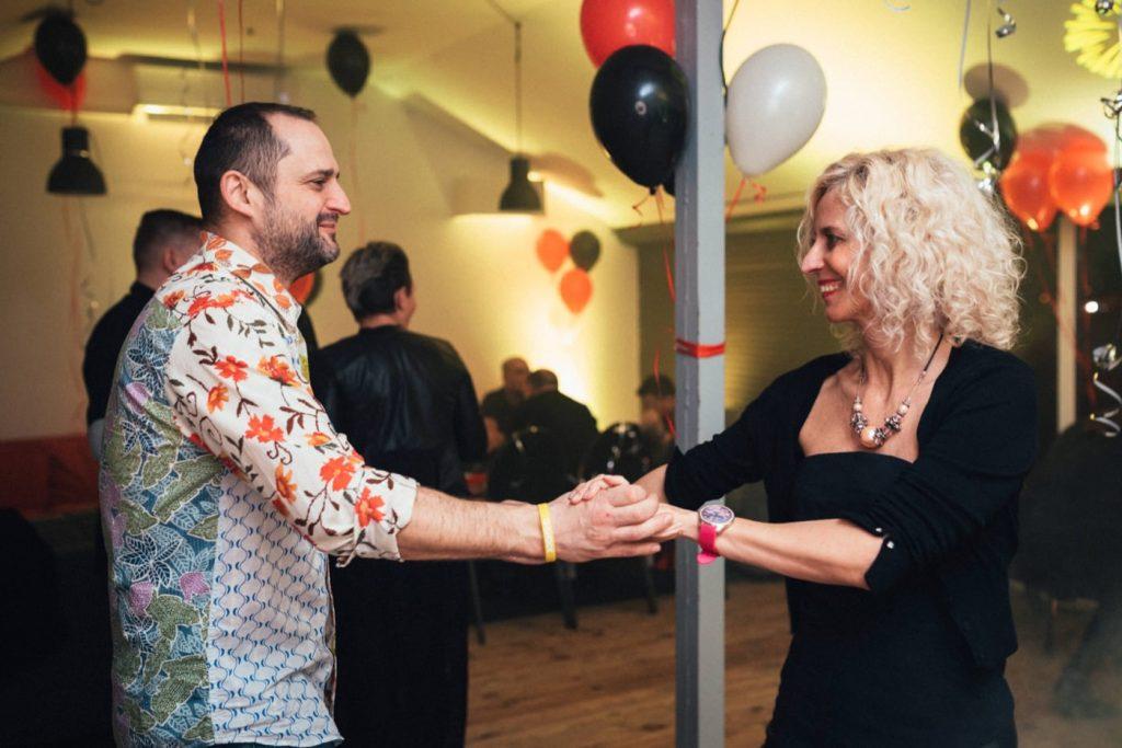 Mężczyzna i kobieta tańczą na tle czerwonych czarnych i białych balonów w żółtym świetle