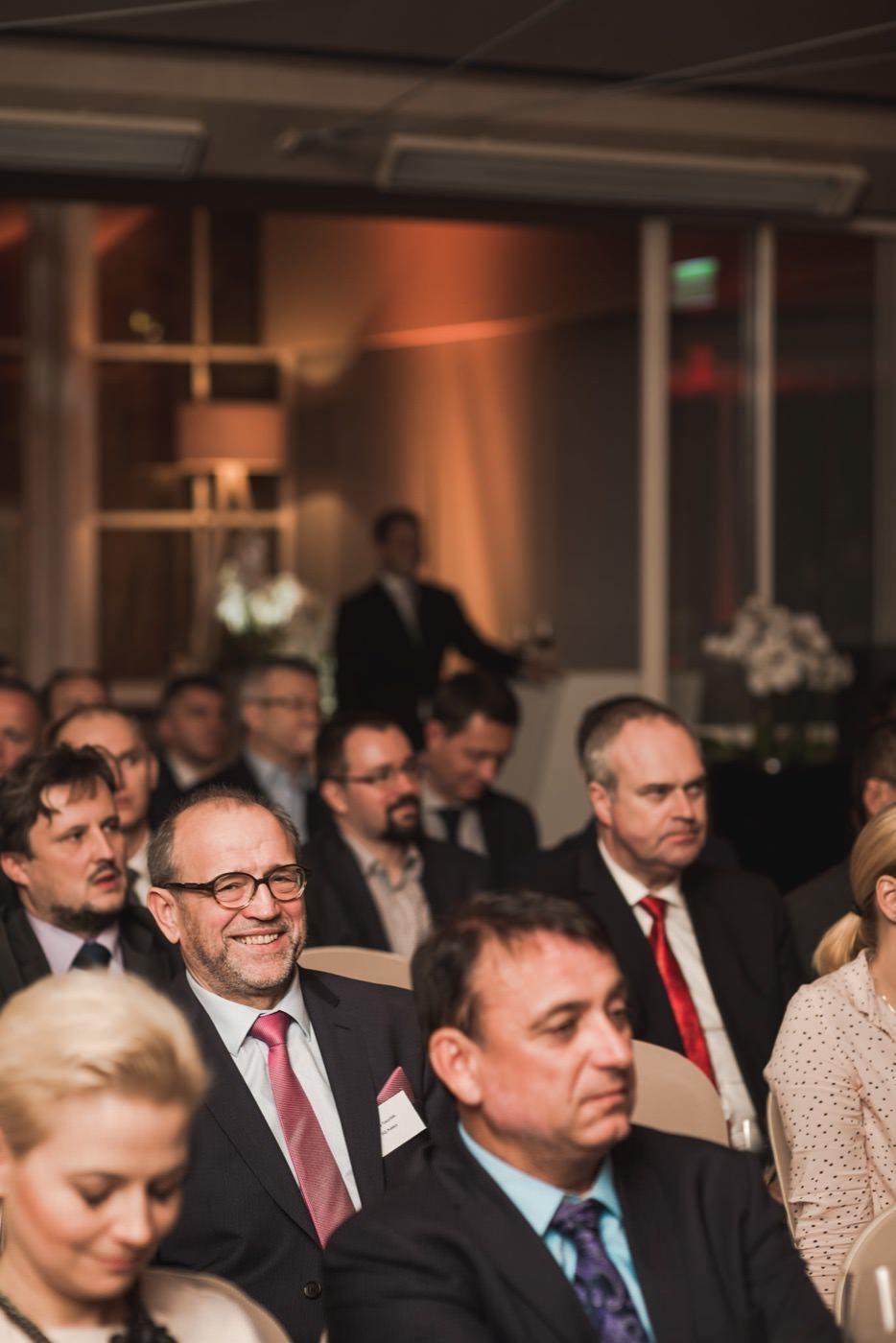 Mężczyzna w okularach uśmiecha się na publiczności