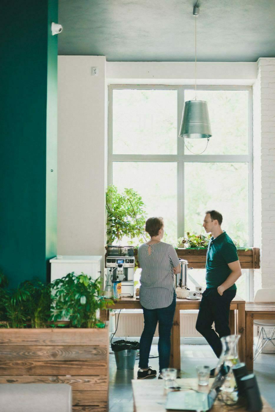 Kobieta i mężczyzna rozmawiają w zielonym pomieszczeniu z wysokimi oknami i lampą zrobioną z wiadra