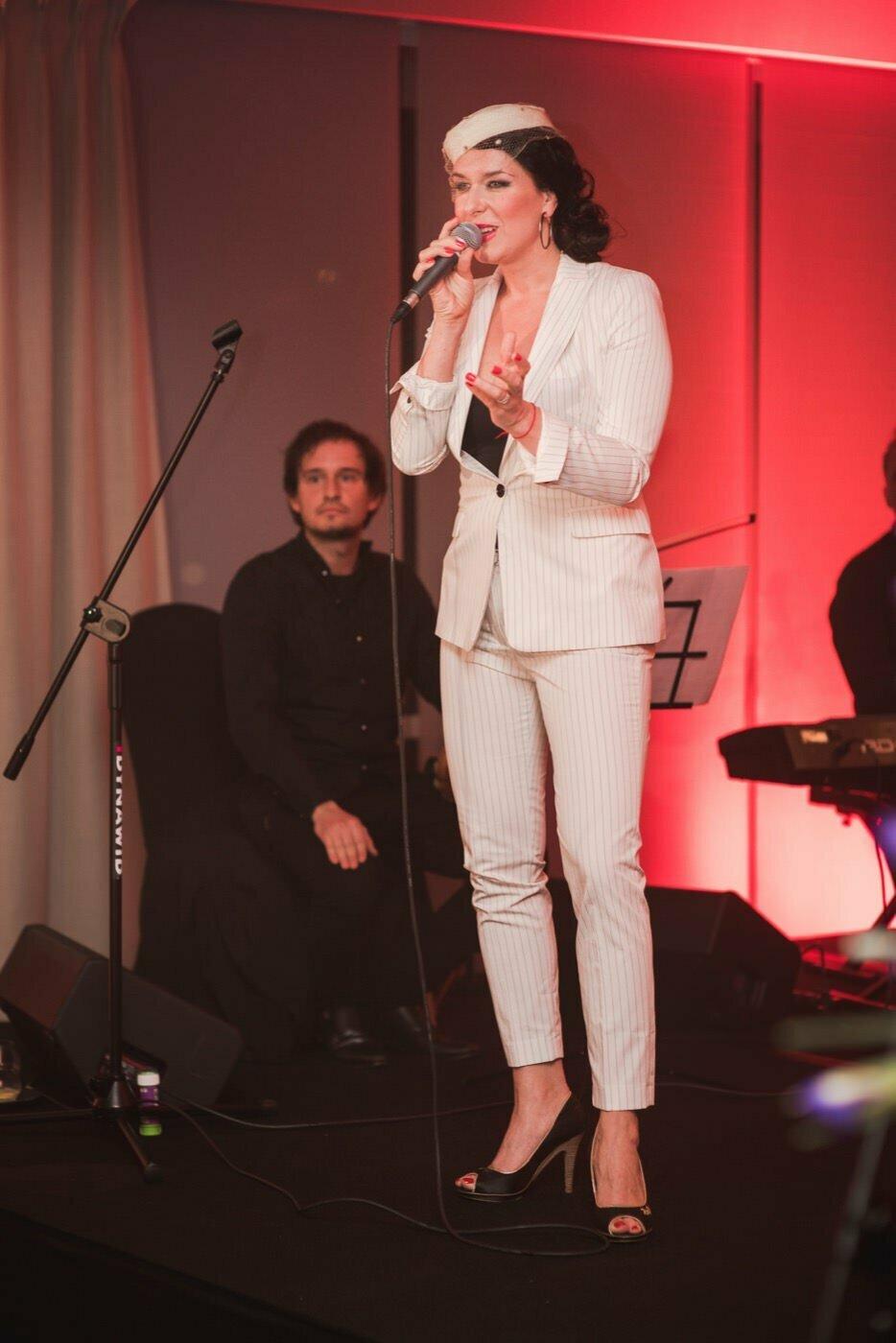 Kobieta w białym garniturze w paski z mikrofonem na scenie
