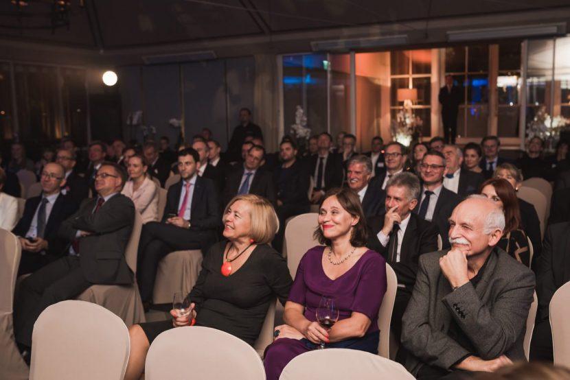 Publiczność w pierwszym rzędzie uśmiecha się podczas występu