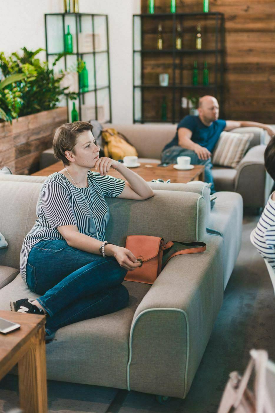 Kobieta w bluzce w paski siedzi na kanapie