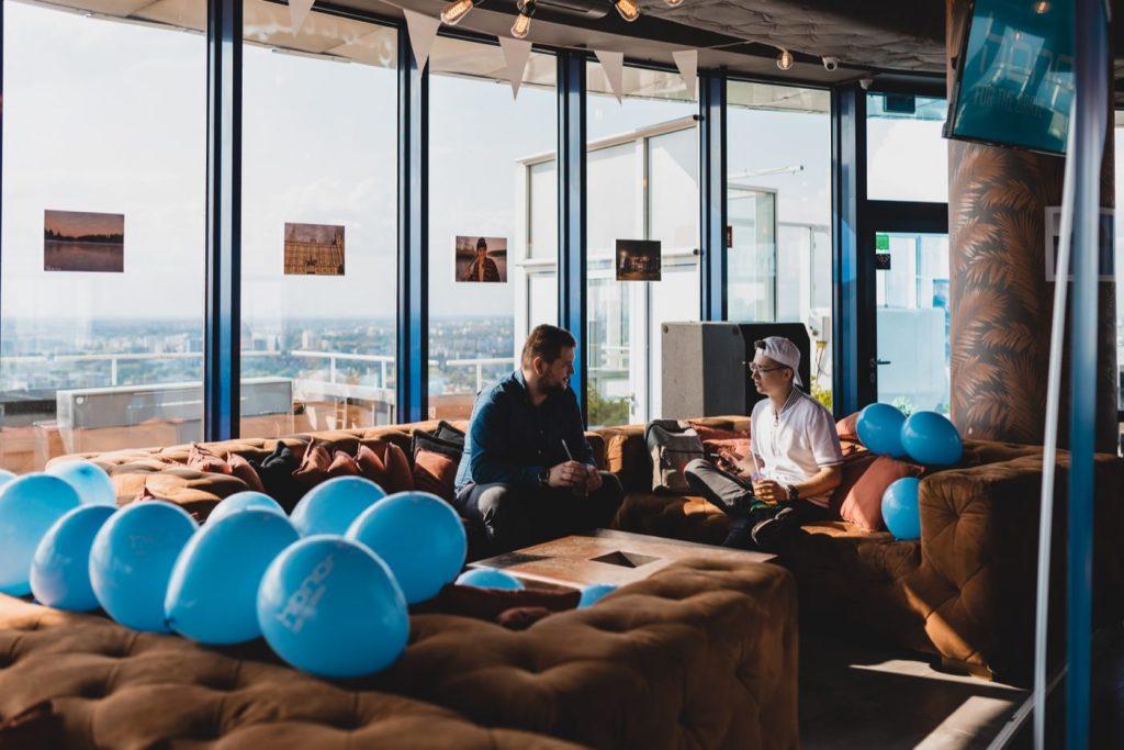 Mężczyżni na kanapie w klubie level 27 otoczeni niebieskimi balonami
