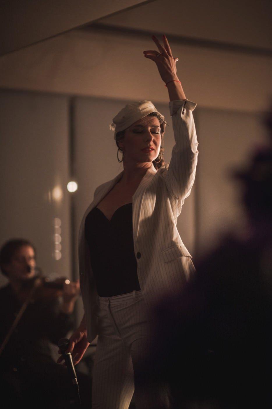 Kobieta na scenie z uniesioną ręką i zamkniętymi oczami w kontrastowym świetle