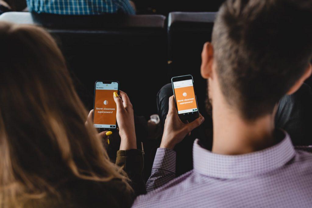 Ludzie trzymający telefony z Quizem kahoot