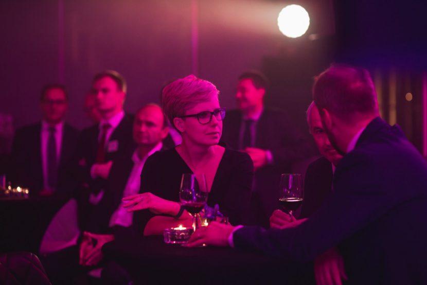 Kobieta w okularach rozmawia przy stoliku w fioletowym świetle