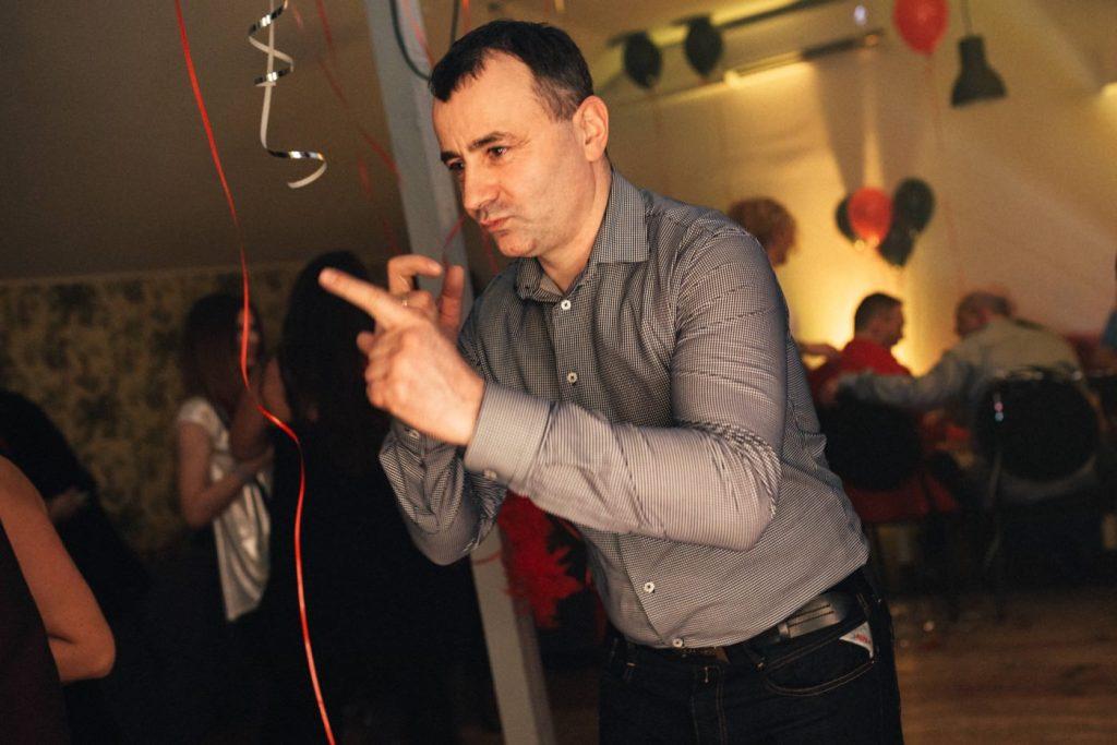 Mężczyzna w szarej koszuli tańczy w przystanku wisła