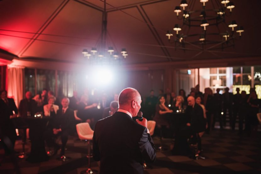 Prowadzący przemawia ze sceny w restauracji Belvedere