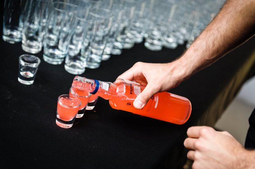 Ręka nalewającym czerwoną wódkę