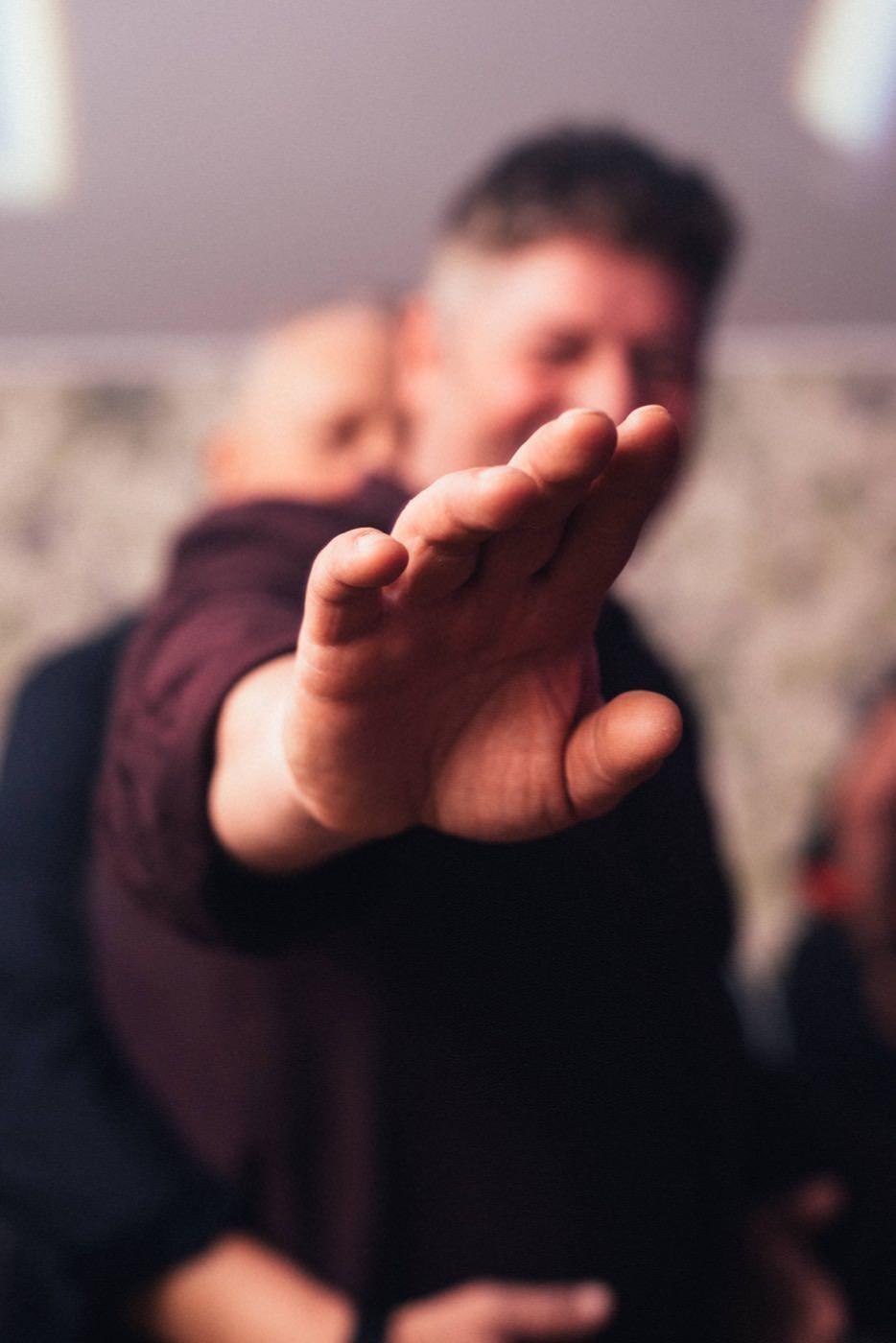 Mężczyzna wyciąga rękę do obiektywu