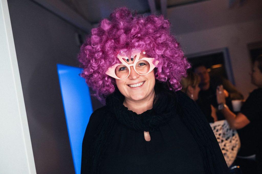 Kobieta w fioletowej peruce i dużych okularach