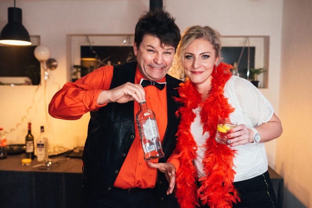 Mężczyzna w czerwonej koszuli i kobieta w czerwonym szalu trzymają wódkę