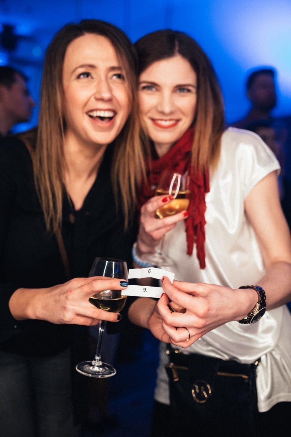 Dziewczyny trzymają kieliszki z winem i kartki z cyframi 6 9
