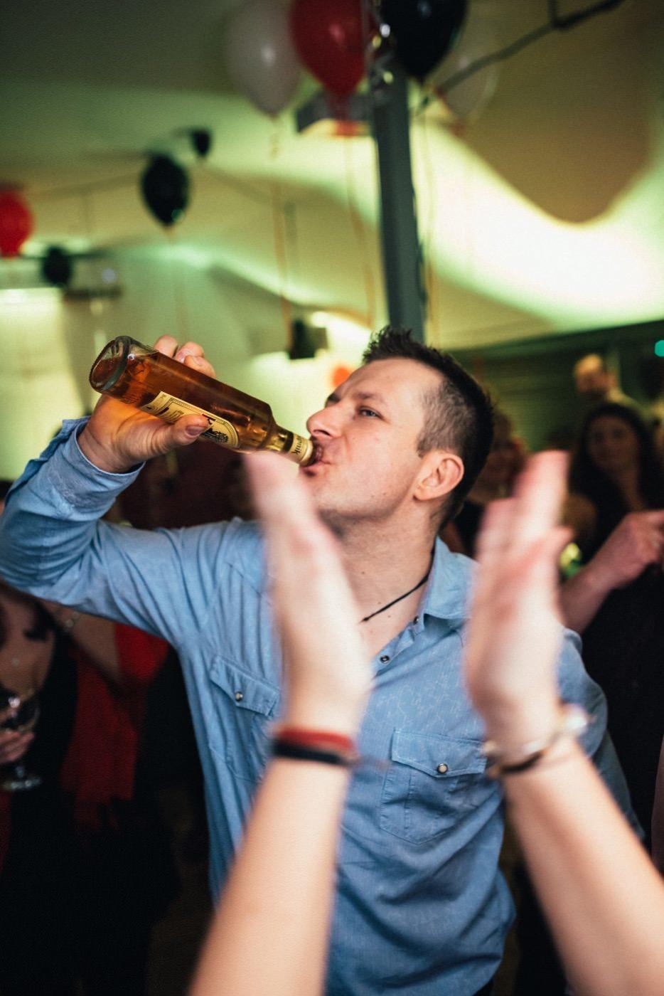 Mężczyzna w jeansowej koszuli pije piwo na parkiecie
