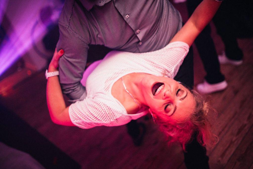 Kobieta w białek koszulce odchyla się w tańcu
