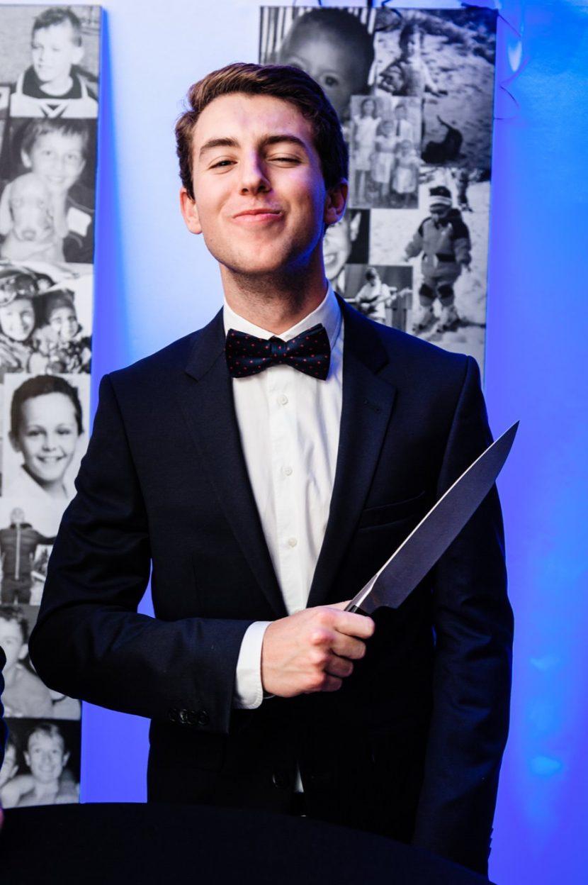 Chłopak w garniturze pokazuje z nożem do zdjęcia