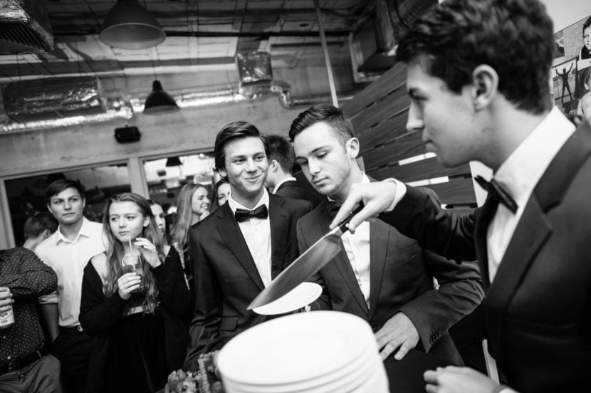 Solenizanci kroją tort urodzinowy aby rozdać gościom