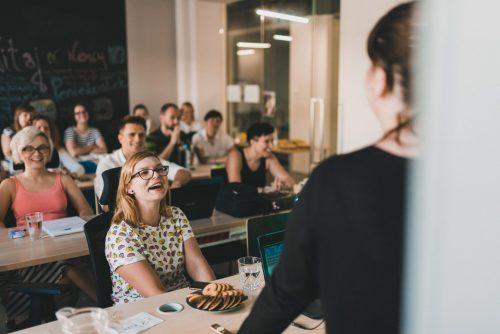 Fotorelacja ze szkolenia - Dziewczyna w okularach przy talerzu z ciasteczkami śmieje się na szkoleniu