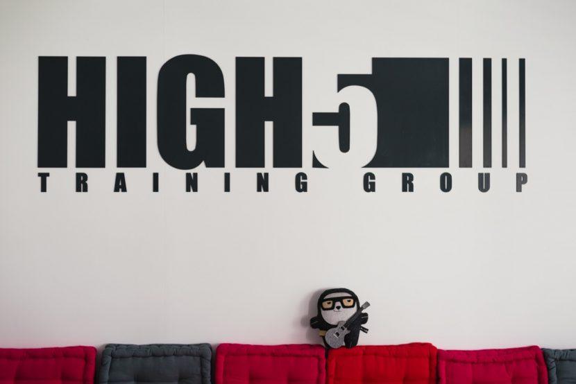 Logo firmy naścianie i miś z gitarą na czerwonej kanapie