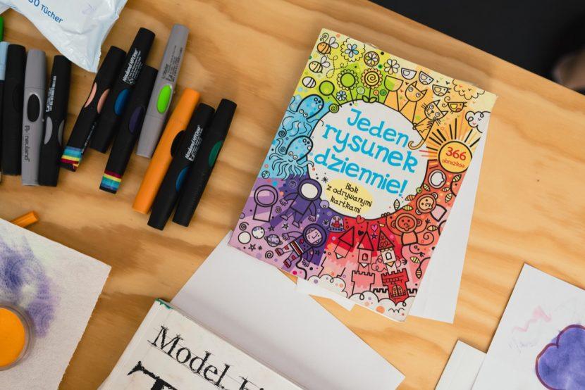 Książka Jeden Rysunek Dziennie na stole z markerami