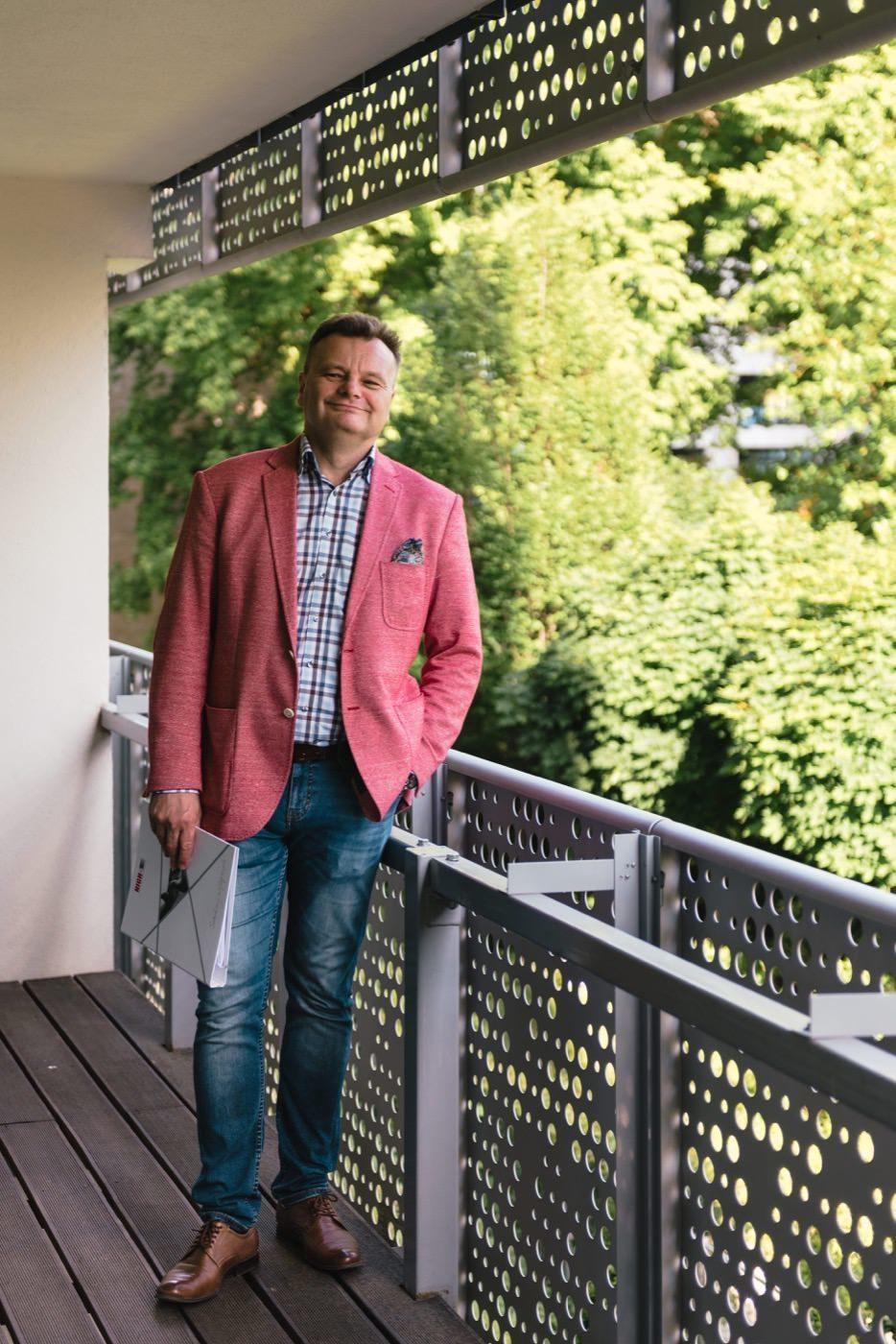 Mężczyzna w różowej marynarce stoi na balkonie