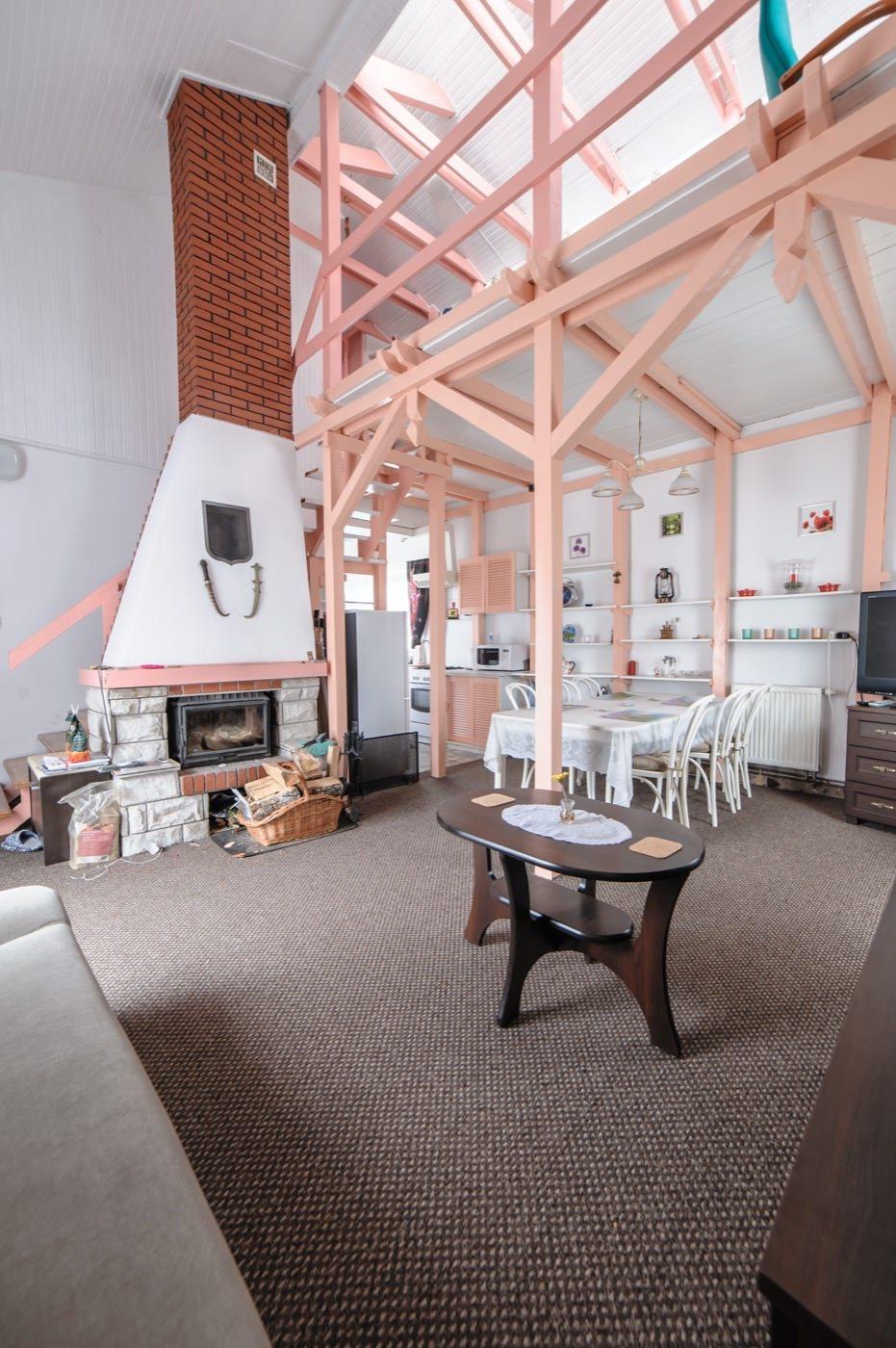 Zdjęcia domu na sprzedaż - salon z antresolą i kominkiem