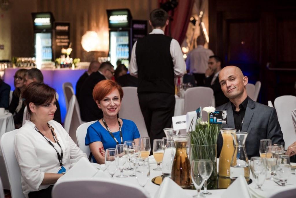 Dwie kobiety i mężczyzna przy białym stole