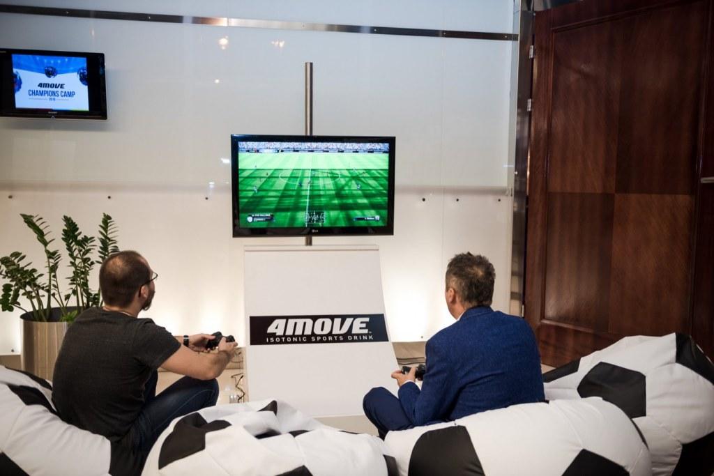 Mężczyżni na pufach w kształcie piłek grają w fifę na konsoli playstation